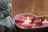 buddha statue and a stoneheart, filled with water rose petals and candles