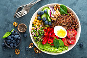 Buddha bowl dinner with boiled egg, chickpea, fresh tomato, sweet pepper, cucumber, savoy cabbage, red onion, green sprouts, spinach leaves, blueberry, walnuts, chia and quinoa. Healthy dish, lunch bo