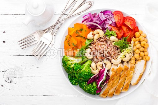 Buddha bowl dish with chicken fillet, brown rice, pepper, tomato, broccoli, onion, chickpea, fresh lettuce salad, cashew and walnuts. Healthy balanced eating. Top view. White background : Stock Photo