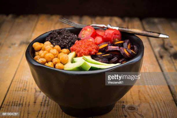 Buddha bowl of black amaranth, avocado, Purple Haze, roasted chickpeas, tomatoes and ajvar