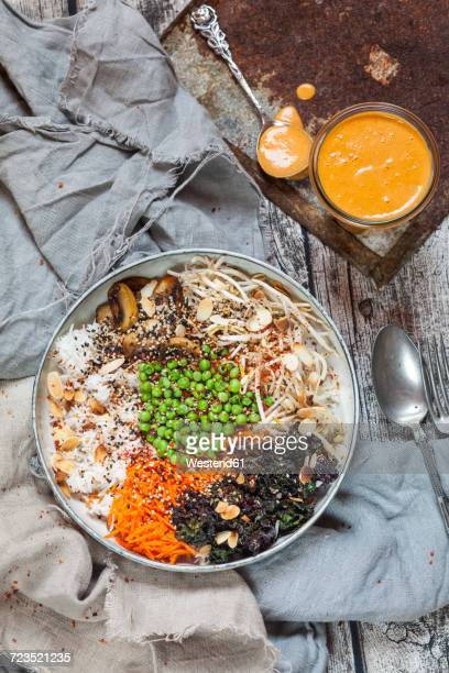 Buddha bowl of kalette, carrot, mung bean sprouts, rice, peas, button mushrooms, and roasted almonds