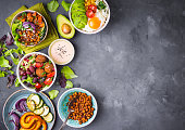 Mixed healthy vegetarian salads with vegetables, sweet potato, falafel, bulgur, avocado, eggs. Assorted buddha bowl salads background. Healthy dinner. Salad in bowl. Making ingredients. Space for text