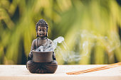 Buddha figurine with incense, selective focus