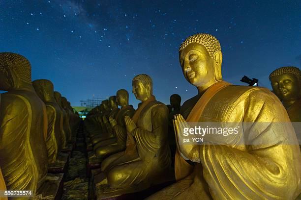 buddha statue and night sky with milky way