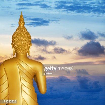 Buddha statue at sunset. Rear view. : Stock Photo