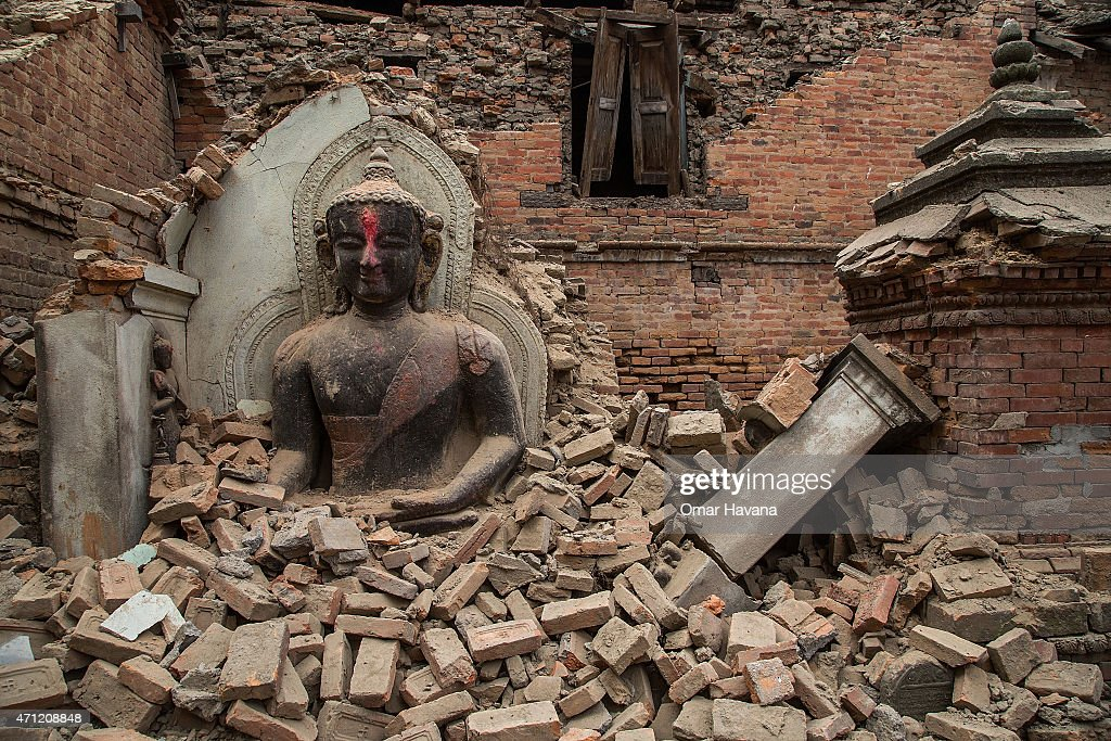 Buddha statue is surrounded by debris from a collapsed temple in the UNESCO world heritage site of Bhaktapur on April 26 2015 in Bhaktapur Nepal A...