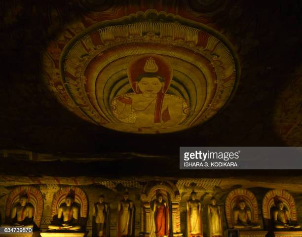 Buddha statues are seen underneath a painted roof in a natural cave at Rock Temple also known as the Rangiri Dambulla Rajamaha Viharaya in Dambulla...