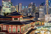 The famous Buddha Tooth Relic Temple in China town, Singapore. A stunning Chinese-style architecture among tall buildings with city lights.