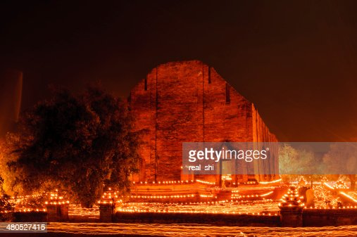Buddhism walk with lighted candles trail around ancient temple : Stockfoto