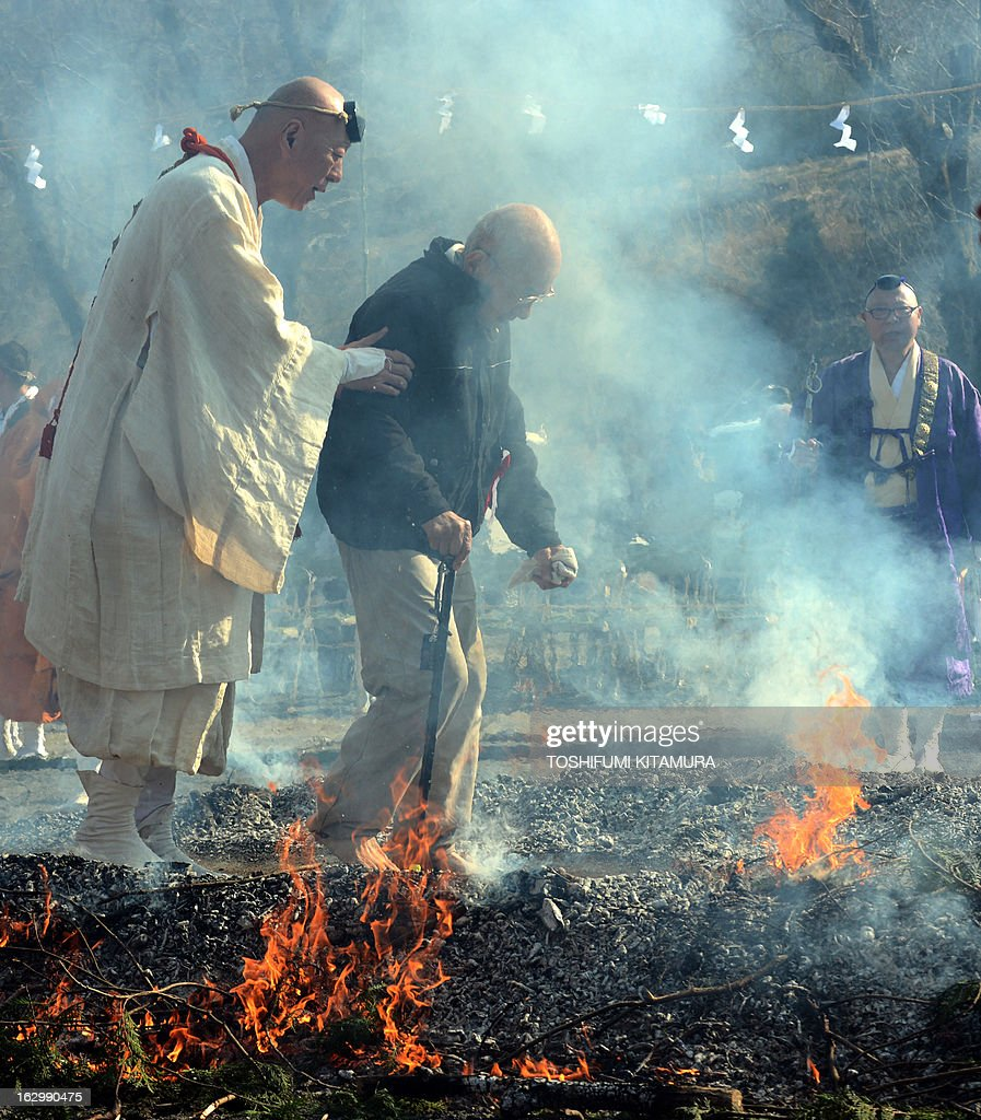 A Buddhist ascentic monk leads an elderly man as he walks barefoot through flames during the 'Hi-watari', or fire walking ceremony, to herald the coming of spring at the Fudoji temple in Nagatoro town, Saitama prefecture on March 3, 2013. Thousands of people watched and joined the fire walking ritual to purify the mind and body and to pray for safety.