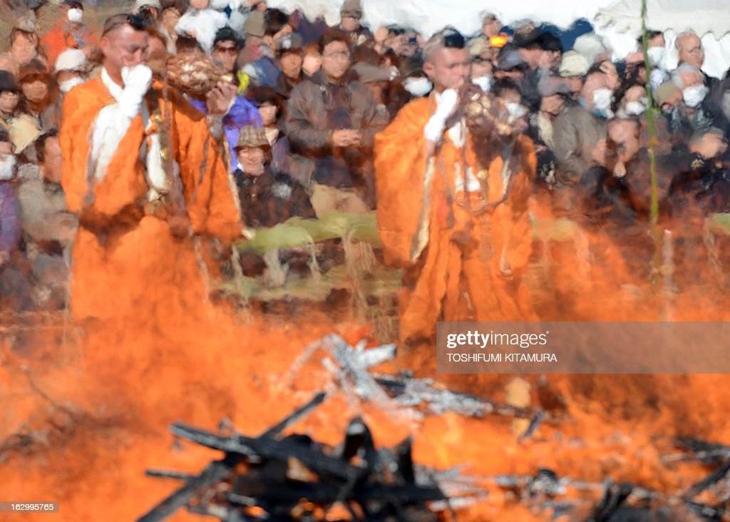 Buddhist ascentic monks blow trumpet shells during the 'Hi-watari', or fire walking ceremony, to herald the coming of spring at the Fudoji temple in Nagatoro town, Saitama prefecture on March 3, 2013. Thousands of people watched and joined the fire walking ritual to purify the mind and body and to pray for safety.