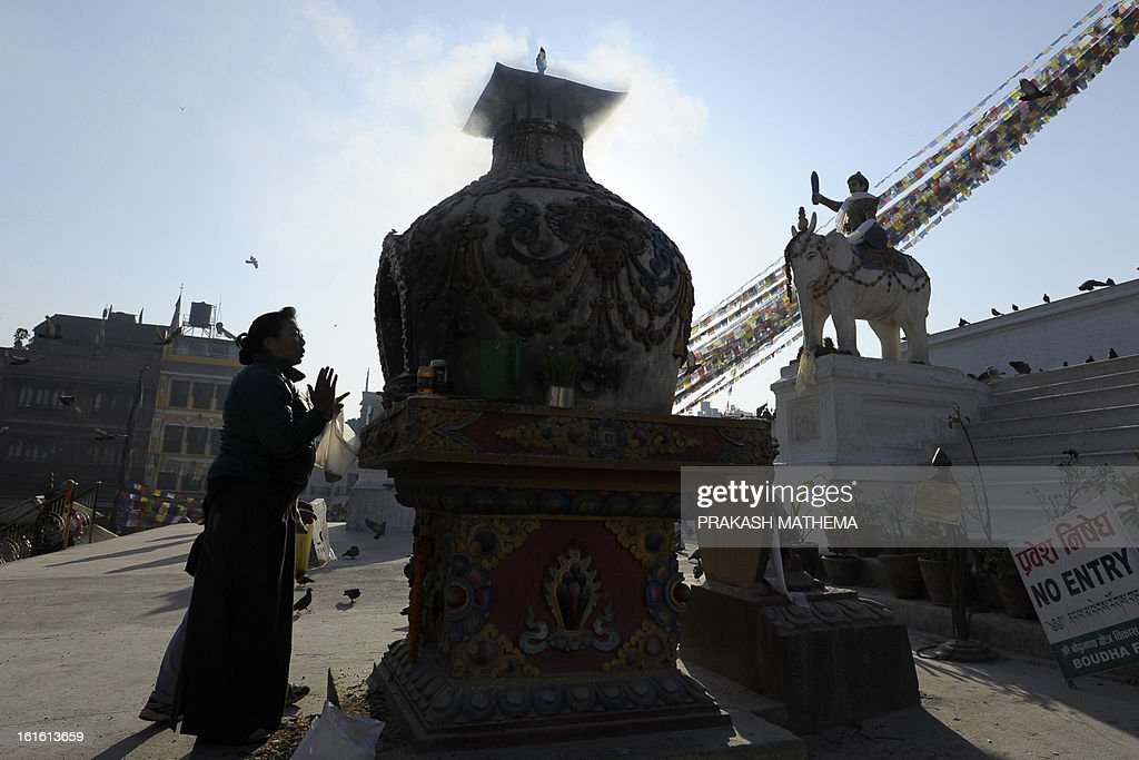 A Buddhist devotee burns incense at the Boudhanath Stupa - close to where a monk self-immolated against Chinese rule in Tibet - on the third day of Losar, the Tibetan new year, in Kathmandu on February 13, 2013. A Tibetan monk doused himself in petrol in a Kathmandu restaurant on Wednesday and set himself on fire, marking the 100th self-immolation bid in a wave of protests against Chinese rule since 2009. AFP PHOTO/Prakash MATHEMA