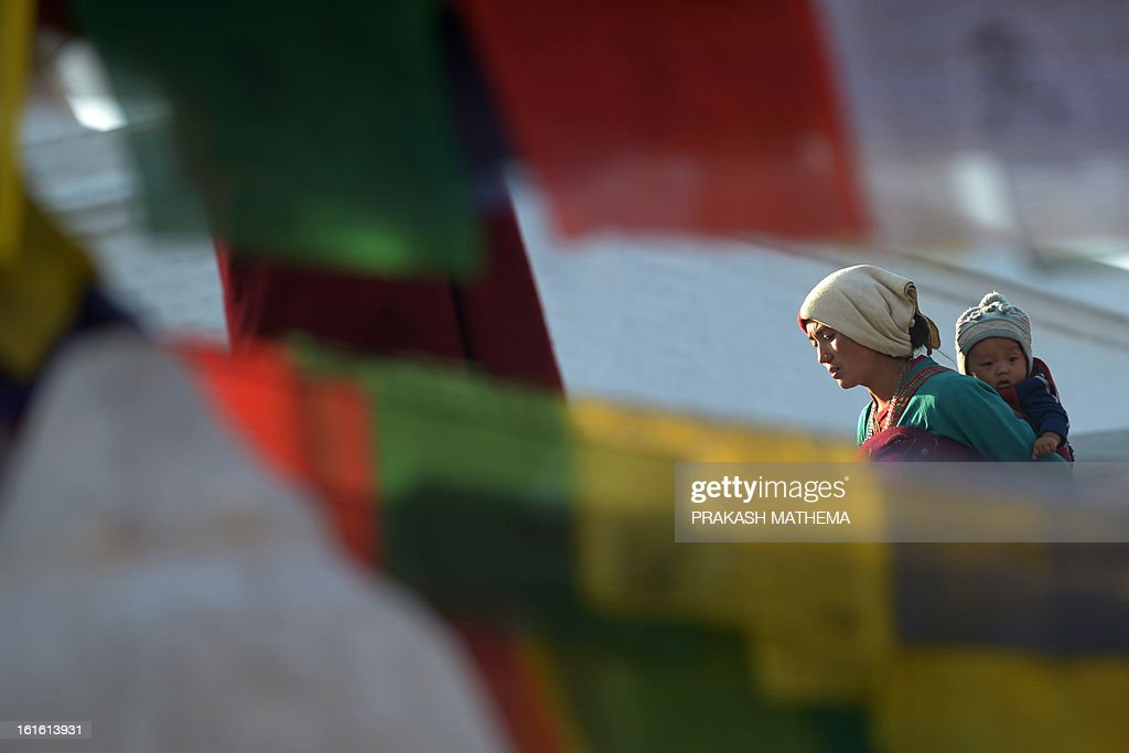 A Buddhist devotee circumambulates the Boudhanath Stupa - close to where a monk self-immolated later in the day against Chinese rule in Tibet - on the third day of Losar, the Tibetan new year, in Kathmandu on February 13, 2013. A Tibetan monk doused himself in petrol in a Kathmandu restaurant on Wednesday and set himself on fire, marking the 100th self-immolation bid in a wave of protests against Chinese rule since 2009. AFP PHOTO/Prakash MATHEMA