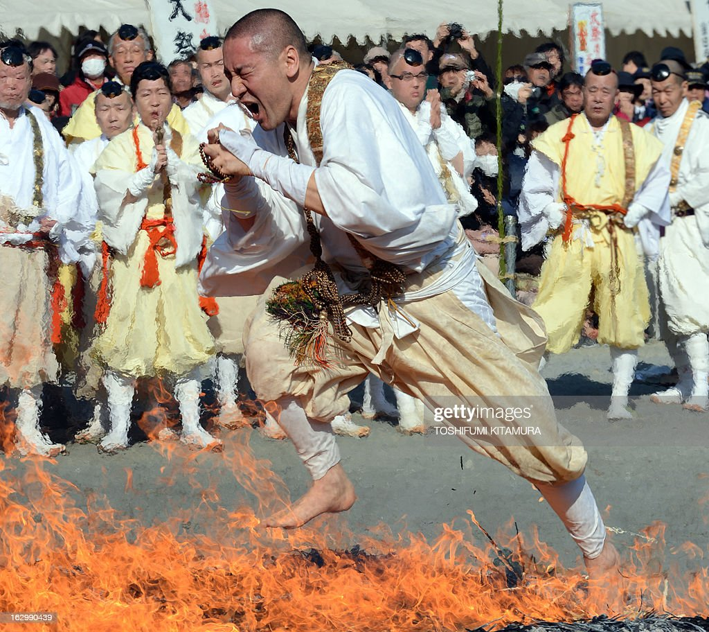 A Buddhist devotee dashes barefoot through flames during the 'Hi-watari', or fire walking ceremony, to herald the coming of spring at the Fudoji temple in Nagatoro town, Saitama prefecture on March 3, 2013. Thousands of people watched and joined the fire walking ritual to purify the mind and body and to pray for safety. AFP PHOTO/TOSHIFUMI KITAMURA