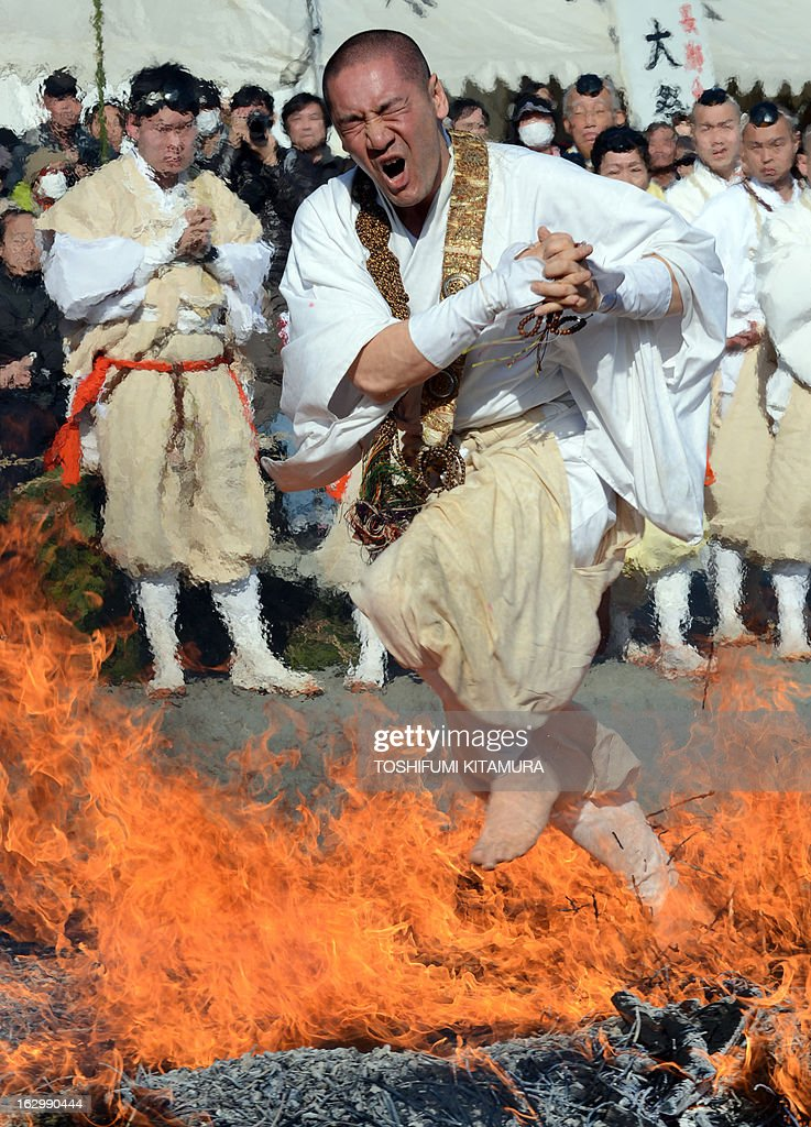 A Buddhist devotee dashes barefoot through flames during the 'Hi-watari', or fire walking ceremony, to herald the coming of spring at the Fudoji temple in Nagatoro town, Saitama prefecture on March 3, 2013. Thousands of people watched and joined the fire walking ritual to purify the mind and body and to pray for safety.