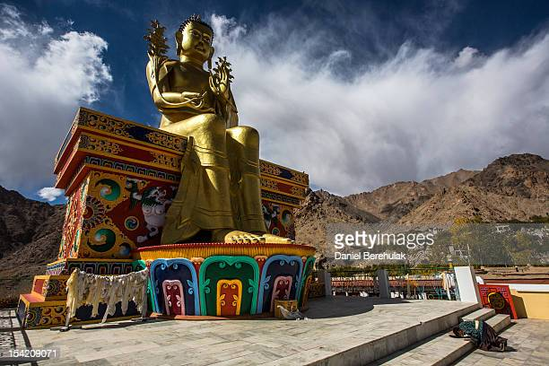 Buddhist devotee prays at the base of a 25m stautue of Buddha at the Likir monastery on October 4 2012 near to Leh in Ladakh India Ladakh nestled...
