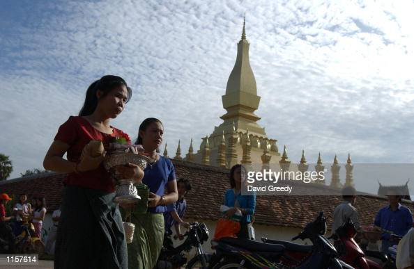 Buddhist devotees bring offerings to monks at a monastery outside Pha That Luang to celebrate Khao Phansa or the beginning of the Buddhist's Lent in...