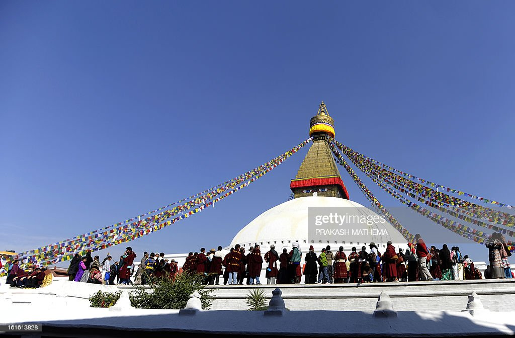 Buddhist devotees gather the Boudhanath Stupa - close to where a monk self-immolated later in the day against Chinese rule in Tibet - on the third day of Losar, the Tibetan new year, in Kathmandu on February 13, 2013. A Tibetan monk doused himself in petrol in a Kathmandu restaurant on Wednesday and set himself on fire, marking the 100th self-immolation bid in a wave of protests against Chinese rule since 2009. AFP PHOTO/Prakash MATHEMA