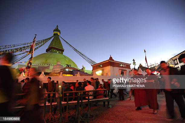 Buddhist devotees walk in front of the Boudhanath Stupa during a full moon festival in Kathmandu on October 29 2012 The Boudhanath Stupa which was...