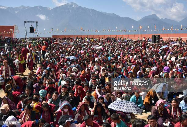 Buddhist followers listen as exiled Tibetan spiritual leader the Dalai Lama speaks at the Yiga Choezin ground in the district of Tawang in India's...