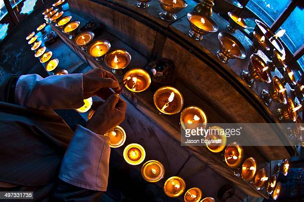 A Buddhist lights a butter lamp and offers prayers in a monastery in the Himalaya.