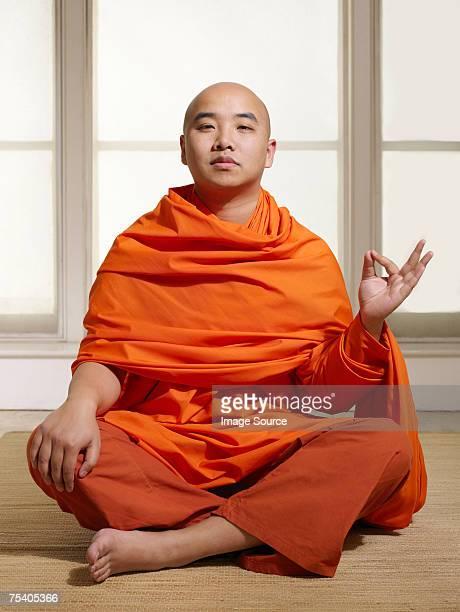 Buddhist man making a hand gesture
