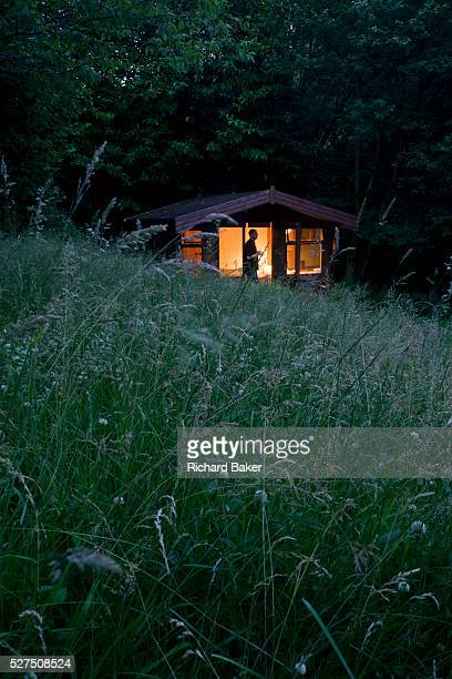 A Buddhist man on silent retreat in a private cabin at the Rivendell Buddhist Retreat Centre East Sussex England As the last light from a summer's...