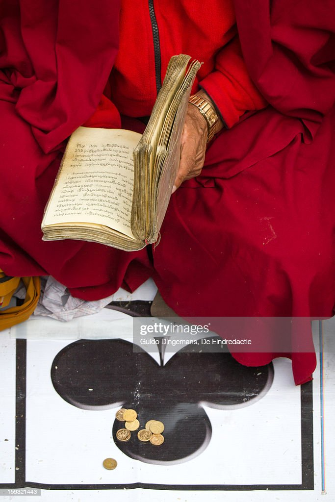 Buddhist monk, ace of clubs & small change : Stock Photo