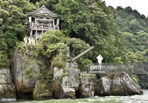 A Buddhist monk at Isakiji Temple jumps into Lake Biwa from a thick square 13meterlong pole during the annual pole diving event at Omihachiman in...