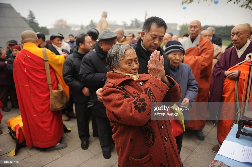 A Buddhist monk (back L) blesses Nanjing massacre survivors and their relatives as they pay their respects to victims on the 75th anniversary of the Nanjing massacre at the Memorial Museum in Nanjing on December 13, 2012. Air raid sirens sounded in the Chinese city of Nanjing on December 13 as it marked the 75th anniversary of the mass killing and rape committed there by Japanese soldiers -- with the Asian powers' ties at a deep low. AFP PHOTO/Peter PARKS