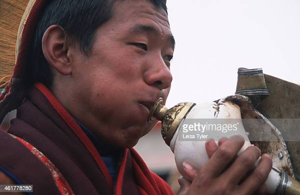 Buddhist monk blows into a conch shell an object sacred to Tibetan Buddhists during the birthday celebration of Guru Rimpoche at a small monastery in...