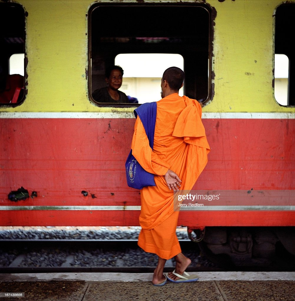 A Buddhist monk chats with a fellow passenger as they wait for the start of the 14-hour train ride through the countryside between Phnom Penh and Battambang. Cambodia's train system is the mode of transport for the poorest of the poor in a country defined by poverty - and yet the government has cut back passenger service for increased cargo transport. The rolling stock started off its Cambodian career as cast-offs from various European railroads. Now, it is at best dilapidated, at worst bullet-scarred and unusable. As foreign investment pours into the country after years of turmoil, almost none of it goes to refurbish this basic transport link..