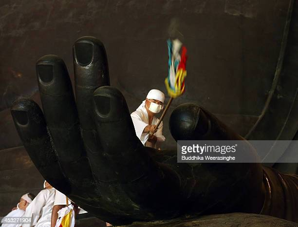 Buddhist monk cleans the dust off of the 15meterhigh Great Buddha's hand at the Todaiji Temple on August 7 2014 in Nara Japan About 100 Buddhist...