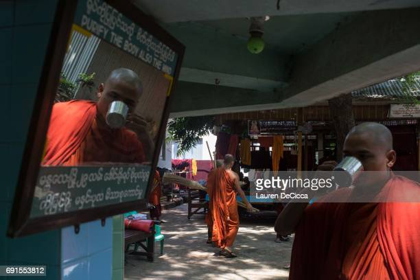 Buddhist Monk from the Masoeyein Monastery takes a drink near a mirror that says 'purify the body and also the mind' on June 1 2017 in Mandalay Burma...