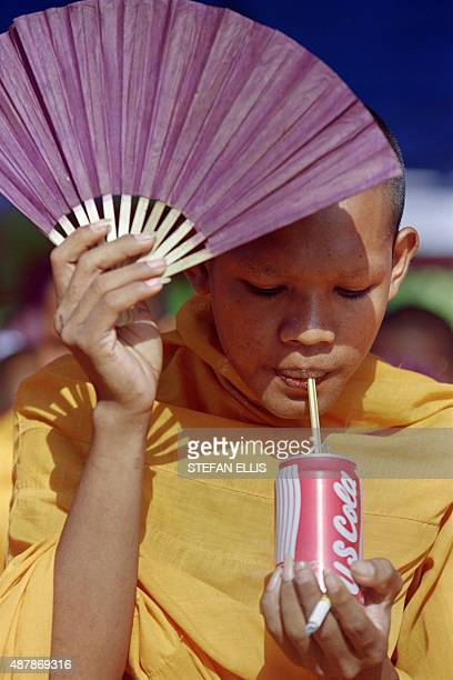 A Buddhist monk holding a fan and a cigarette drinks in a Coke can on May 16 in Phnom Penh