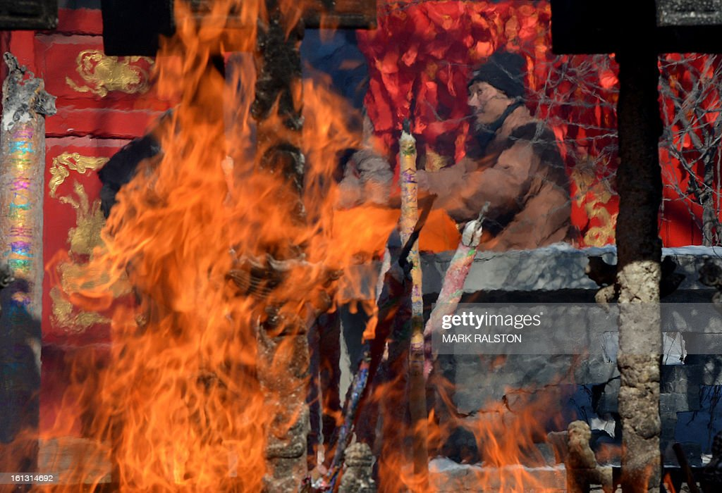 A Buddhist monk holds consultations behind burning joss sticks while worshippers pray at the Baoshan Temple during Lunar New Year celebrations in the Chinese border town of Dandong on February 10, 2013. Revellers across the city lit fireworks and prayed as China traditionally welcomed in the 'Year of the Snake'. AFP PHOTO/Mark RALSTON