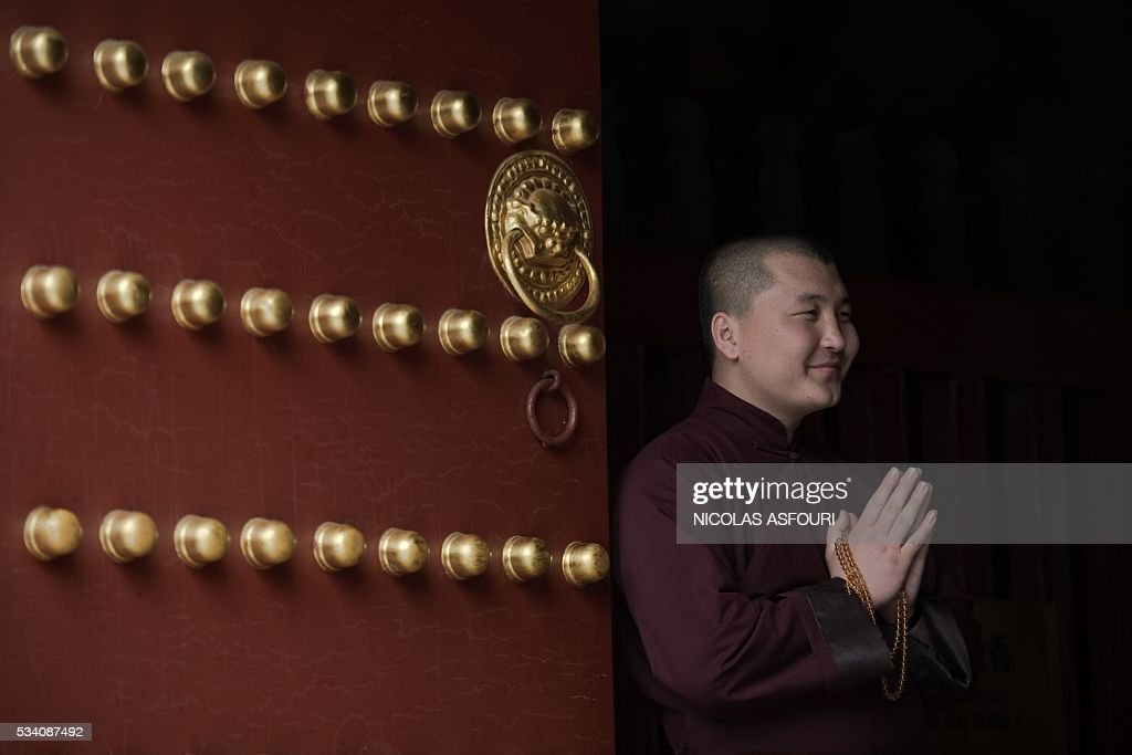A Buddhist monk joins his hands inside the Lama temple in in Beijing on May 25, 2016. / AFP / NICOLAS