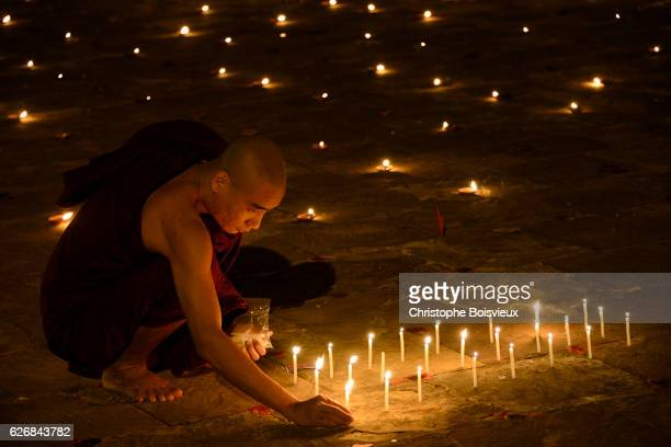 Buddhist monk lighting candles. Thadingyut festival of lights. Ananda temple. Bagan. Myanmar.