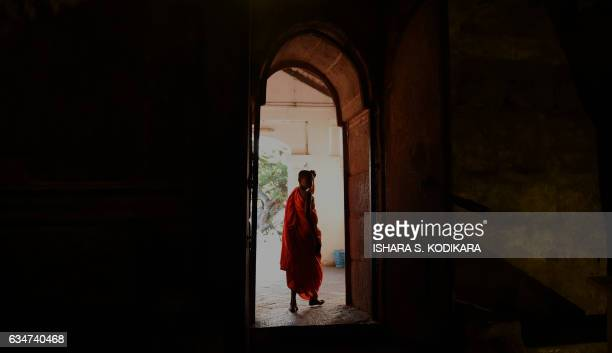 Buddhist monk looks over into a natural cave at the Rock Temple also known as the Rangiri Dambulla Rajamaha Viharaya in Dambulla some 150 kms north...