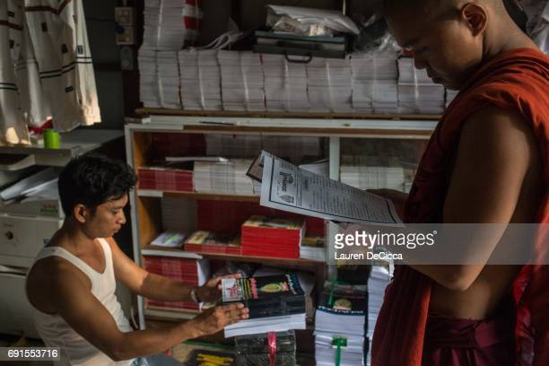 Buddhist monk looks through a nationalist magazine published by the Masoeyein Monastery which spreads hate speech and propaganda against the Muslim...