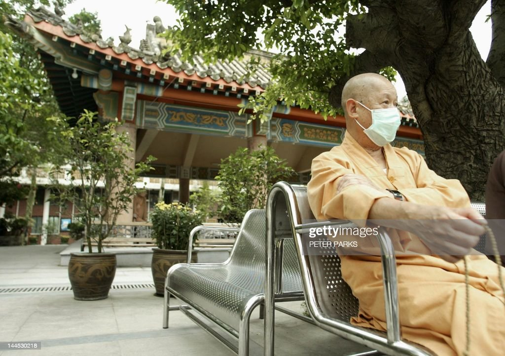 A Buddhist monk plays with his prayer beads at Po Lin Monastary on Lantau Island, Hong Kong wearing a mask to protect against a killer outbreak of pneumonia known as Severe Acute Respiratory Syndrome (SARS), 30 April 2003. Buddhists start a week celebrations of the birth of Buddah 01 May with festivities at Po Lin Monastry, home of the largest seated outdoor bronze Buddha in the world. AFP PHOTO/Peter PARKS