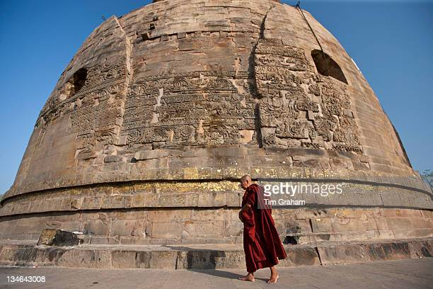 Buddhist monk praying as he walks around Dhamakh Stupa at Sarnath ruins near Varanasi Benares Northern India