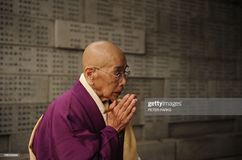 A Buddhist monk prays at a wall inscribed with the names of Nanjing massacre victims on the 75th anniversary of the Nanjing massacre at the Memorial Museum in Nanjing on December 13, 2012. Air raid sirens sounded in the Chinese city of Nanjing on December 13 as it marked the 75th anniversary of the mass killing and rape committed there by Japanese soldiers -- with the Asian powers' ties at a deep low. AFP PHOTO/Peter PARKS