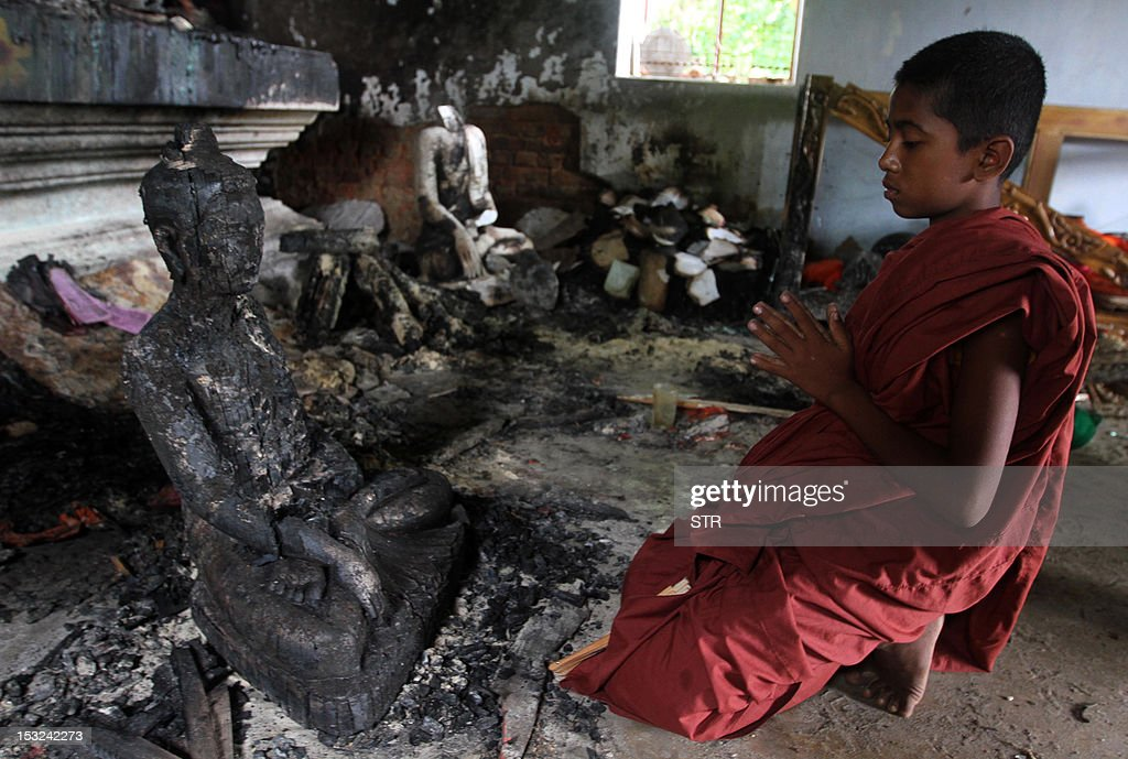 A Buddhist monk prays in a burnt temple in Cox's Bazar, some 396 kilometres (246 miles) from the capital Dhaka on October 2, 2012. Bangladesh police said they had arrested nearly 300 people after Muslim mobs attacked temples and houses in what Buddhist leaders described as the worst violence against the community since independence.