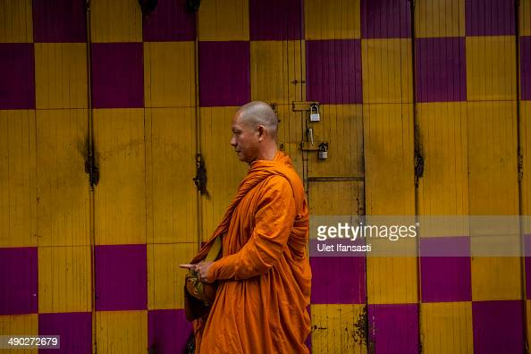 Buddhist monk prepares at a temple before a walk around the streets to receive religious alms from Buddhist followers during Pindapata procession on...