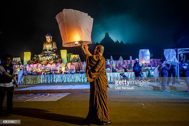 Buddhist monk prepares to release a lantern into the air at Borobudur temple during celebrations for Vesak Day on May 15 2014 in Magelang Central...