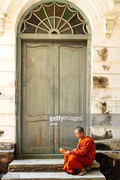 Buddhist  monk reading outside door