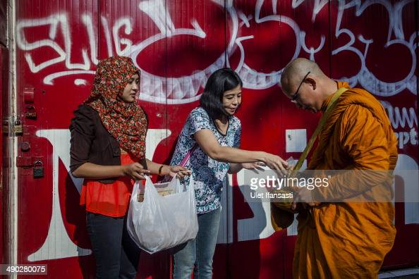 Buddhist monk receives religious alms from a Buddhist follower as they walk around the streets during Pindapata procession on May 14 2014 in Magelang...