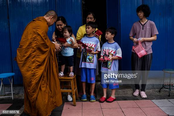 Buddhist monk receives religious alms from Buddhist followers as they walk around the streets during Pindapata procession on May 21 2016 in Magelang...