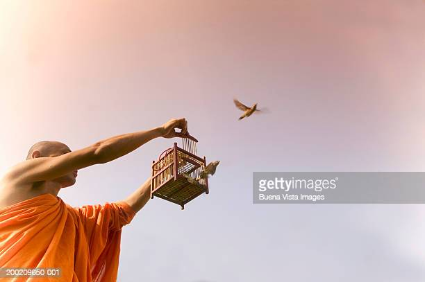Buddhist monk releasing birds from small cage, low angle view